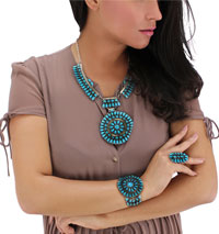 A woman with a turquoise colored necklace and earrings.